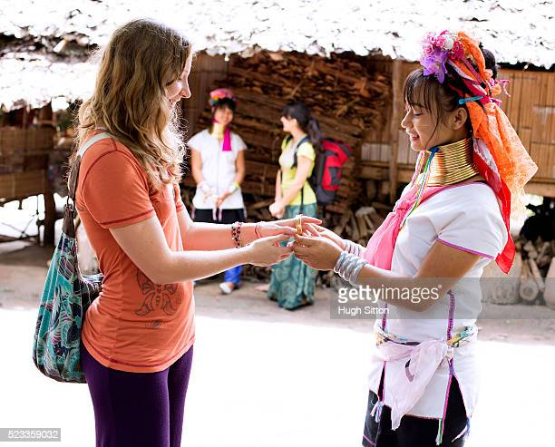 female tourist and local traditionally-dressed woman, chiang mai, thailand - hugh sitton stock pictures, royalty-free photos & images