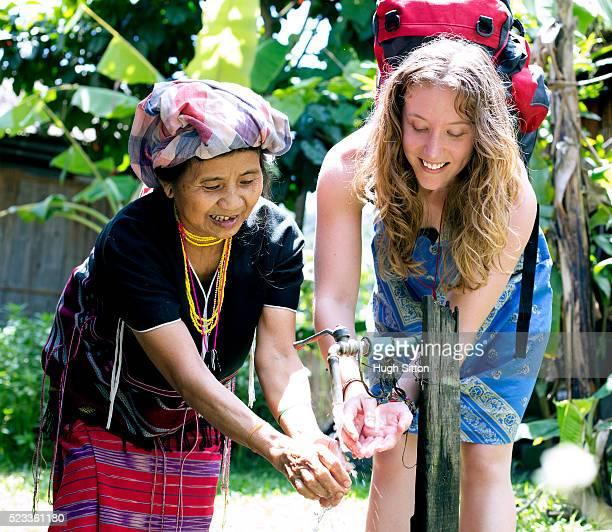 female tourist and senior woman washing hands, chiang mai, thailand - hugh sitton imagens e fotografias de stock