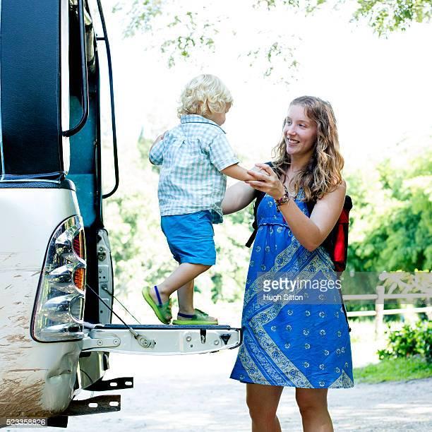 female tourist and son (2-3) disembarking bus - hugh sitton photos et images de collection