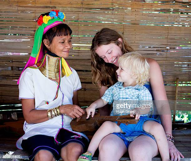 female tourist and son (2-3) meeting hill tribe woman, chiang mai, thailand - hugh sitton stock pictures, royalty-free photos & images