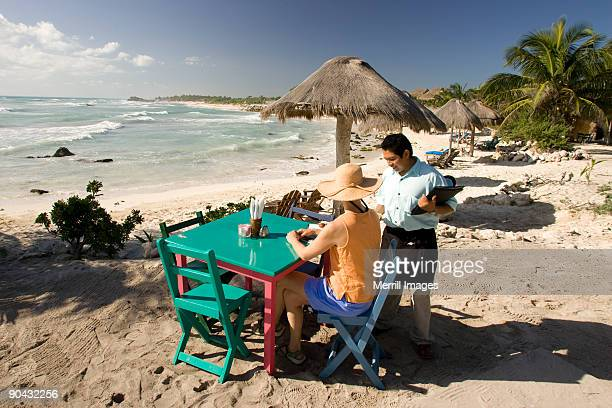 female tourist and waiter at restaurant on beach
