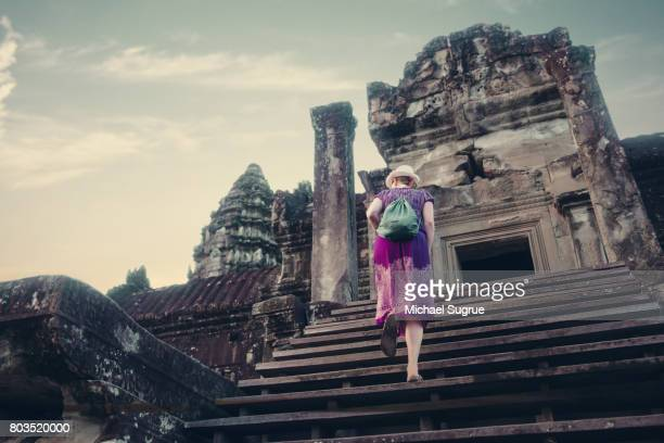 A female tourist ascends the steps outside Angkor Wat Temple, Siem Reap, Cambodia.