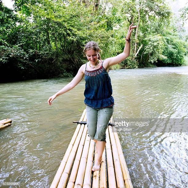 female tourist balancing on wooden raft, chiang mai, thailand - hugh sitton - fotografias e filmes do acervo