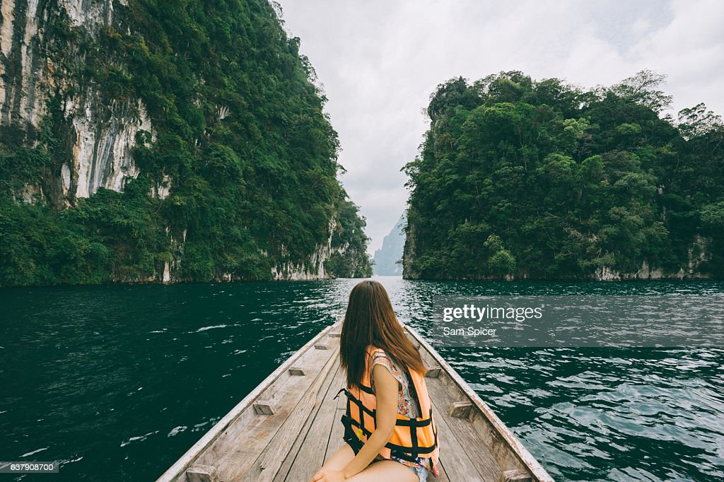 Female tourist exploring lush Jungle lake surrounded by limestone cliffs, Khao Sok National Park, Thailand : Stock Photo