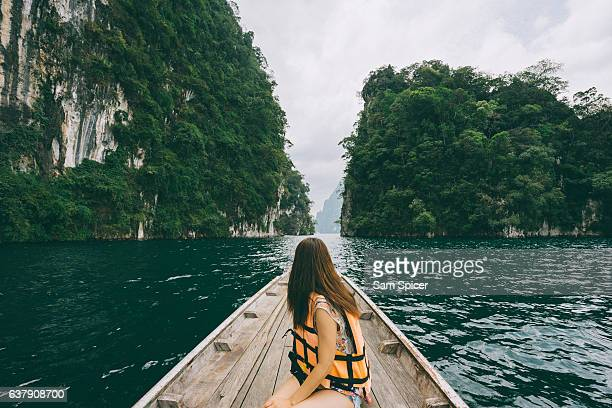 Female tourist exploring lush Jungle lake surrounded by limestone cliffs, Khao Sok National Park, Thailand