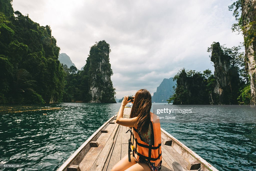 Female tourist exploring lush Jungle lake surrounded by limestone cliffs, Khao Sok National Park, Thailand : Foto de stock