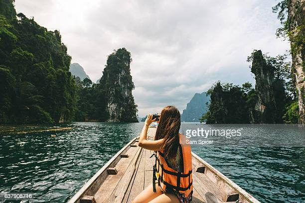 female tourist exploring lush jungle lake surrounded by limestone cliffs, khao sok national park, thailand - south east asia stock pictures, royalty-free photos & images