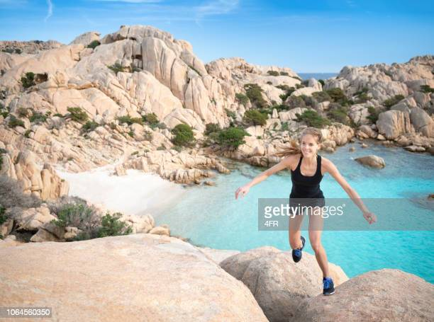 female tourist hiker climbing over rocks to reach the beautiful cala coticcio beach bay, caprera, maddalena, sardinia, italy - sardinia stock pictures, royalty-free photos & images