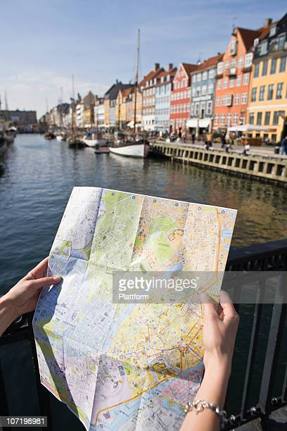 Female tourist holding map at waterfront