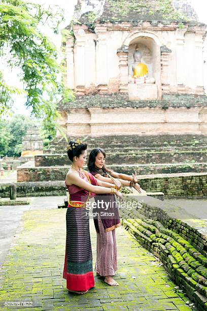 female tourist imitating traditional thai dance, chiang mai, thailand - hugh sitton stock pictures, royalty-free photos & images