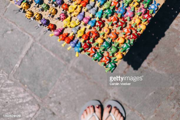 female tourist in flip flops standing in front of small painted mexican figurines lined up for sale on the ground in queretaro, mexico - painting art product stock pictures, royalty-free photos & images
