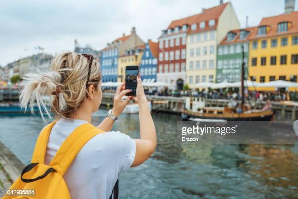 female tourist in nyhavn, copenhagen, denmark - danish culture stock pictures, royalty-free photos & images