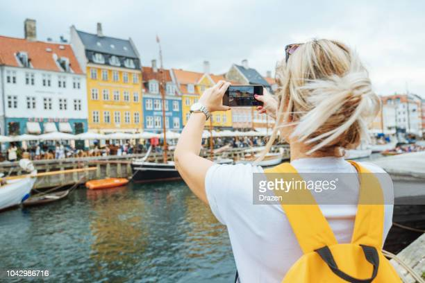 female tourist in nyhavn, copenhagen, denmark - denmark stock pictures, royalty-free photos & images
