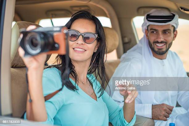 Female tourist in off road vehicle in desert taking photographs, Dubai, United Arab Emirates