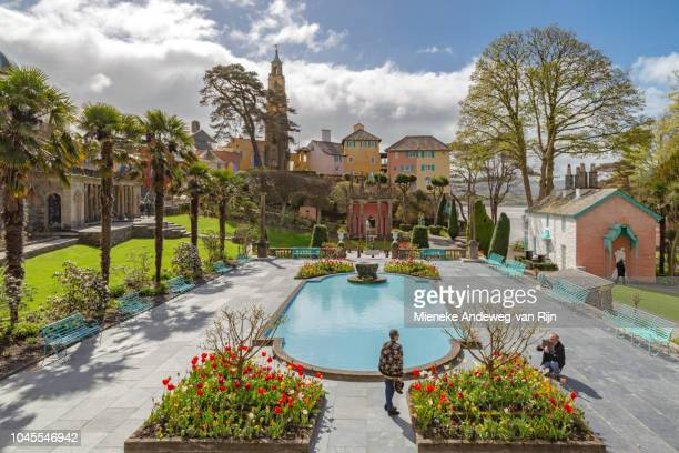 A female tourist is being photographed in the Italianate Portmeirion Village Piazza, Gwynedd, Wales, Wales, United Kingdom