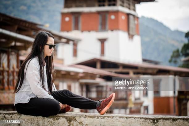 a female tourist is sitting down on a ledge in trongsa dzong, bhutan - trongsa district stockfoto's en -beelden