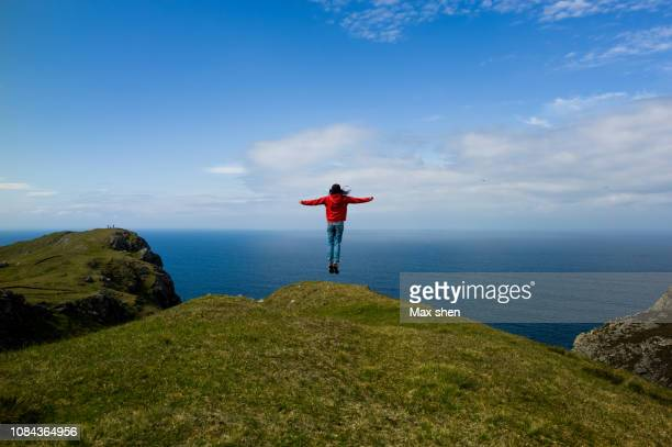 female tourist jumping in the air on the cliff - county donegal stock photos and pictures
