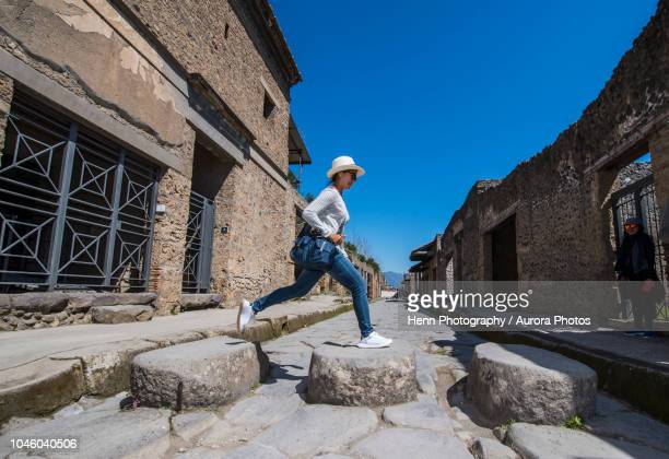 female tourist jumping on stones in ruins of pompeii, naples, italy - pompeya fotografías e imágenes de stock
