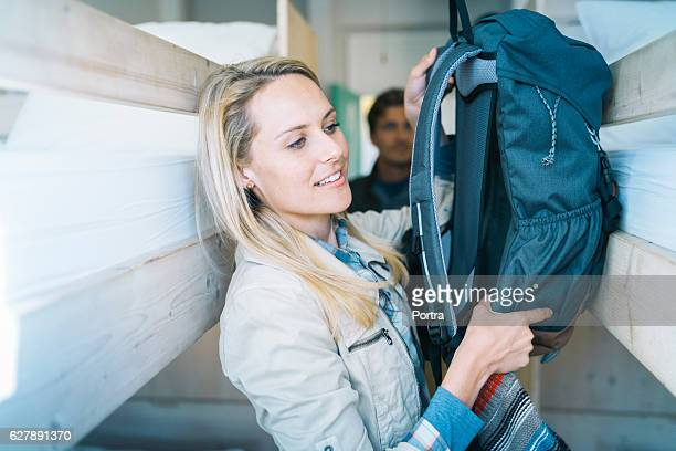 Female tourist keeping backpack on bed in train