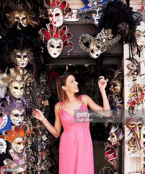 female tourist looking at venetian masks - hugh sitton stock pictures, royalty-free photos & images