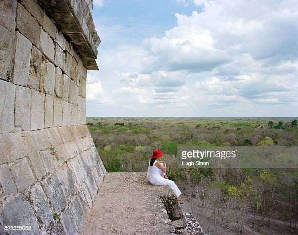 female tourist looking at view from ancient maya pyramid, chichen itza, mexico - hugh sitton stock pictures, royalty-free photos & images