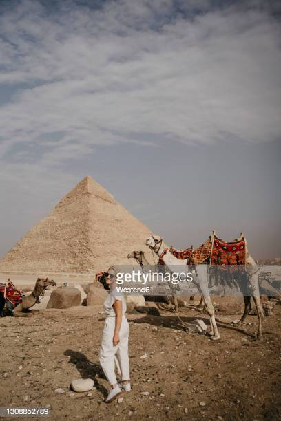 female tourist looking over shoulder at camera in front of great pyramid of giza - looking over shoulder ストックフォトと画像