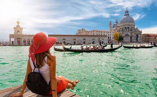 Female tourist looking the Basilica di Santa Maria della Salute and Canale Grande in Venice, Italy 891465194