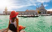 Female tourist looking the Basilica di Santa Maria della Salute and Canale Grande in Venice, Italy