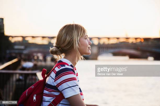 female tourist looks at view of river thames during sunset. - tourism stock pictures, royalty-free photos & images