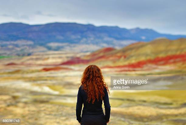 female tourist looks out on painted hills, oregon - painted hills stock pictures, royalty-free photos & images
