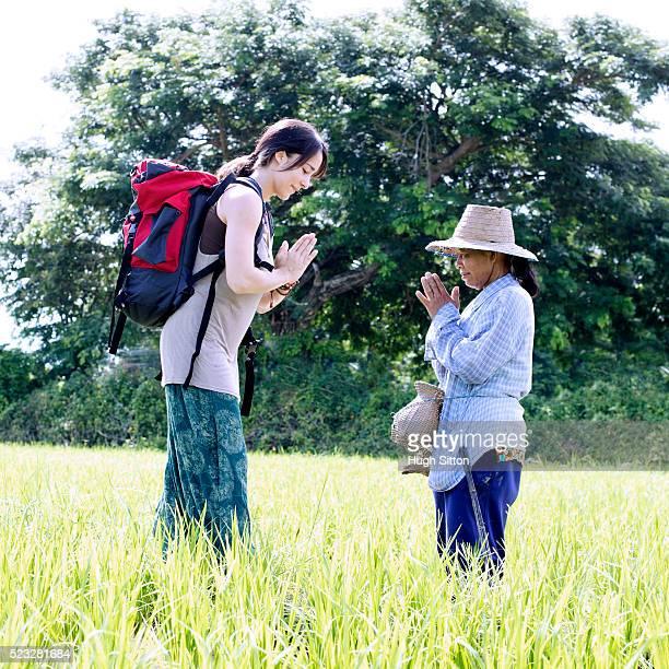 female tourist meeting local farmer, chiang mai, thailand - hugh sitton imagens e fotografias de stock