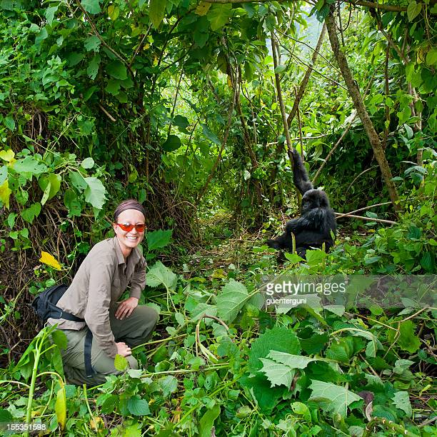Female tourist next to a young Mountain Gorilla in forest