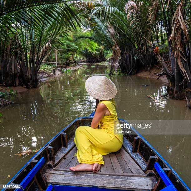 female tourist on boat in mekong river delta, vietnam - vietnam imagens e fotografias de stock