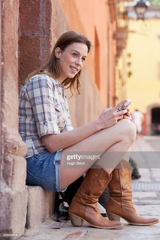 Female tourist on holiday using cell phone : Stock Photo