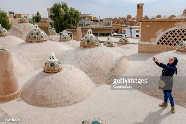 vrouwelijke toeristische fotograaf het vastleggen van een beeld van hamam cupolas op het dak in kashan - cupola stockfoto's en -beelden