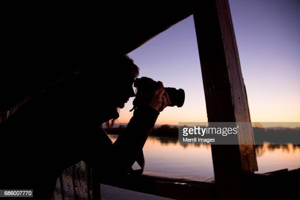 Female tourist photographing at sunset