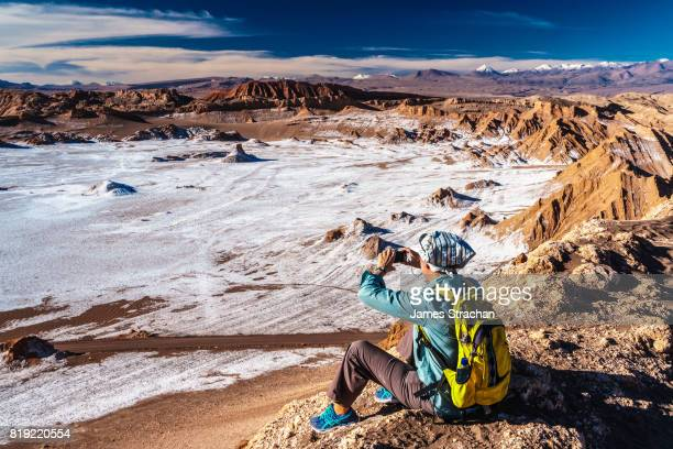 Female tourist photographing the view from the top of the Duna Mayor across the Valley of Moon, Atacama Salt Flats, with snow-capped volcanic peaks in the background, near San Pedro de Atacama, Chile