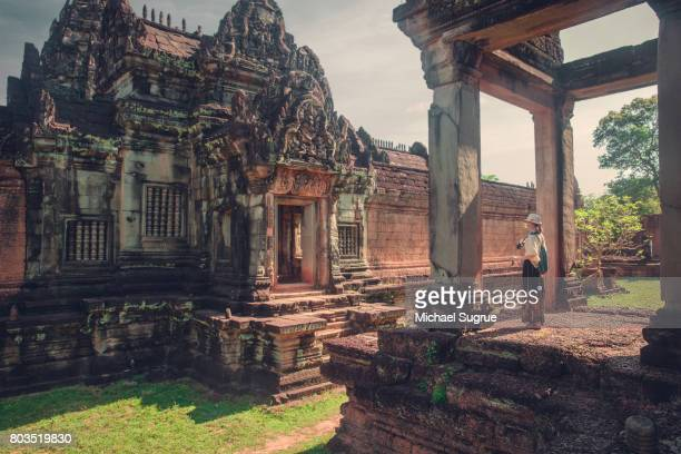 a female tourist photographs banteay samre temple at sunrise, near angkor wat, siem reap, cambodia. - banteay srei stock pictures, royalty-free photos & images