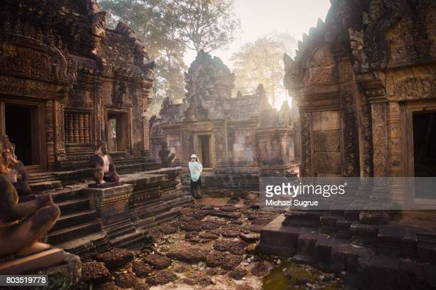 A female tourist photographs Banteay Srei Temple at sunrise, near Angkor Wat, Siem Reap, Cambodia.
