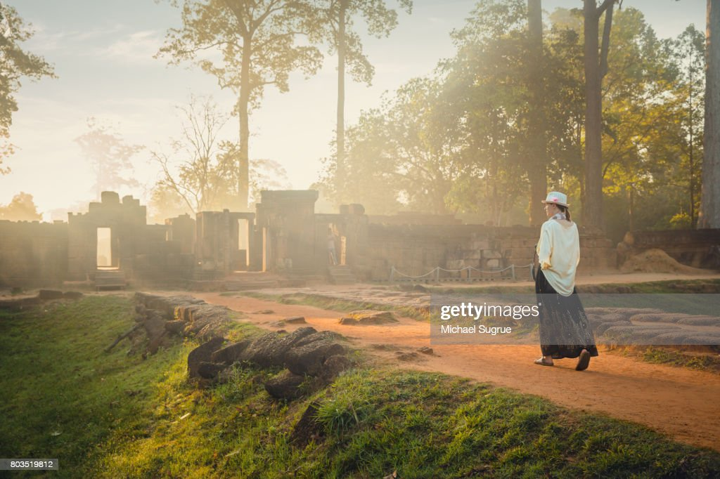 A female tourist photographs Banteay Srei Temple at sunrise, near Angkor Wat, Siem Reap, Cambodia. : Stock Photo