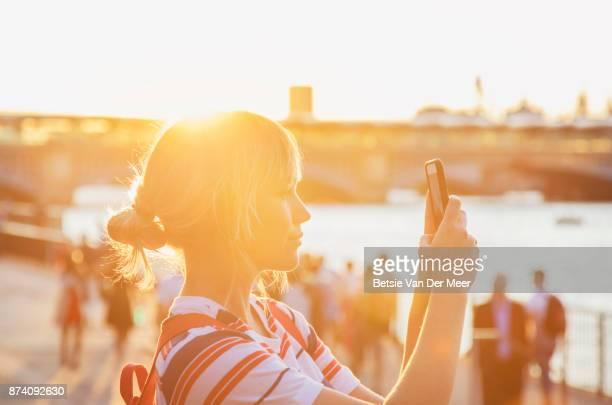 Female tourist photographs city skyline on smart phone.
