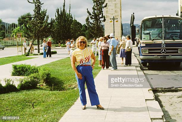 Female tourist posing for a photo with a Mercedes Benz tour bus in the background in front of the Monumento de La Nacion A Sus Proceres in Caracas...