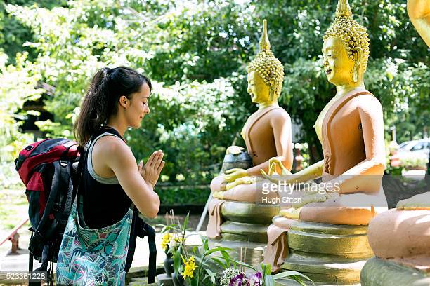 female tourist praying with in front of buddha sculptures, chiang mai, thailand - hugh sitton stock pictures, royalty-free photos & images