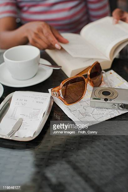 Female tourist reading guidebook at cafe table