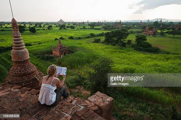 Female tourist reading guidebook at top of buddhist temple, Bagan, Mandalay Division, Myanmar