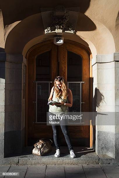Female tourist reading guidebook while standing at doorway