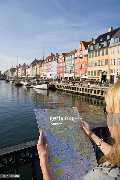 Female tourist reading map at waterfront