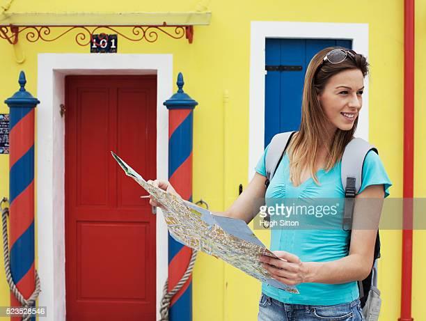female tourist reading map in front of colorful house - hugh sitton stock-fotos und bilder