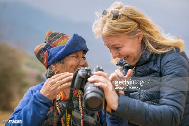 a female tourist shows a bhutanese woman her photo on the back of a camera - bhutan stock pictures, royalty-free photos & images