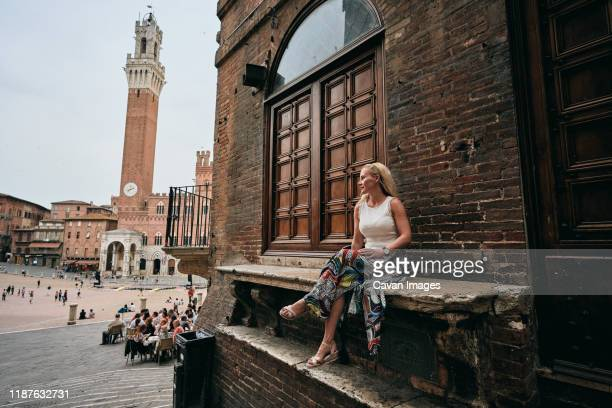 female tourist sitting on bench by old building - siena italy stock pictures, royalty-free photos & images